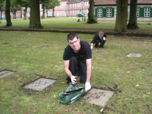 Teilnehmer säubern die Grabsteine am Bassin in Ludwigslust